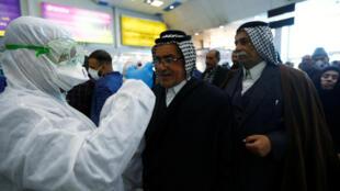 Un membre du personnel médical prend la température des passagers à leur arrivée à l'aéroport de Nadjaf, en Irak, le 21 février 2020.