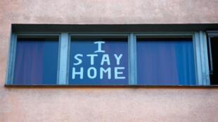 """"""" Je reste à la maison"""" est écrit sur une fenètre dans un appartement berlinois."""