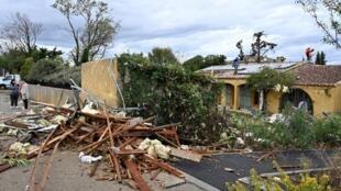 Trabalhadores verificam uma casa depois de uma tempestade em Pont de Crau, perto de Arles, em 15 de outubro de 2019.