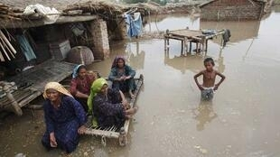 A family sit on a charpoy while a boy stands knee-deep in flood waters in a flooded village in Sukkur in Pakistan's Sindh province.
