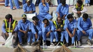 Workers sit on a pavement before entering the Commonwealth Games village