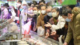 Des habitants de Wuhan portant des masques font leurs achats dans un supermarché, le 10 février 2020.
