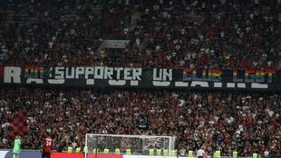 """Nice's supporters display a banner reading """"OM: support an LGBT team to fight against homophobia"""" during the French L1 football match between OGC Nice and Olympique de Marseille (OM) on August 28, 2019 at the """"Allianz Riviera"""" stadium in Nice, southeastern"""