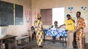 A woman prepares to vote at a local primary school during Benin's parliamentary elections, in the main city of Cotonou, 28 April 2019.