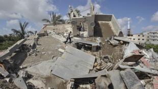Homem caminha sobre escombros de casa que, segundo a polícia de Gaza, foi destruída em um bombardeio israelense nesta terça-feira (15).
