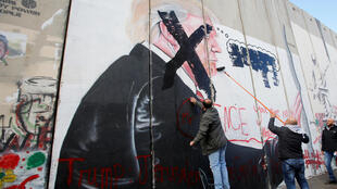 Palestinians deface a mural depicting US President Donald Trump on the Israeli side of the security barrier in Bethlehem, on 7 December, 2017.