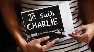 """A demonstrator holds a sign rading """"I am Charlie"""" at a solidarity rally on Wednesday evening"""