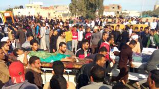 Люди выносят пострадавших в теракте к машинам скорой помощи, 24 ноября 2017.