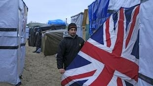 Syrian migrants Terer with a Union Jack sleeping bag used as a door to his shelter in the Jungle