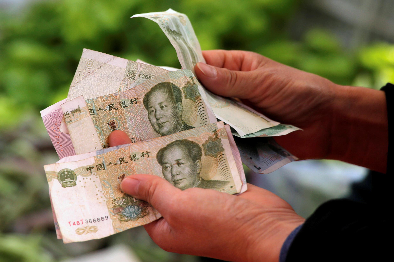 图为一名消费者在一家北京菜市场点数人民币