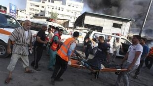Palestinians carry the body of a local Palestinian journalist near a market in Shejaia in the east of Gaza City, 30 July