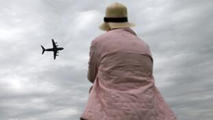 Mulher observa avião passando em Fairford, no Reino Unido.