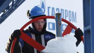 Un ouvrier actioe une vanne à l'usine de traitement du gaz Yuzhno-Priobsky, appartenant à la société Gazpromneft, dans la ville de Khanty-Mansiysk, en Sibérie occidentale, le 28 janvier 2016.