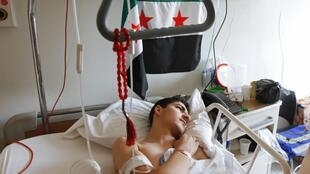 A wounded Syrian man rests while receiving treatment at a hospital in Tripoli, northern Lebanon