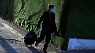 Un voyageur quitte la gare routière de Pékin, le 27 mars 2020 (photo d'illustration).
