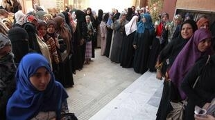 Women queue to cast ballots during the National Assembly election at a polling station in Tripoli