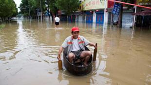 Un résident chinois dans une rue inondée de Chaohu, dans la province d'Anhui, en Chine, le 2 juillet 2016.