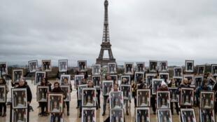 Экоактивисты с перевернутыми портретами Эмманюэля Макрона, вынесенными из мэрий французских коммун, площадь Трокадеро, Париж.