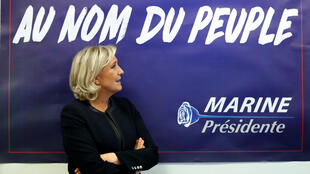 """""""In the name of the people"""", National Front (FN) leader Marine Le Pen in front of a poster for her 2017 French presidential election campaign"""