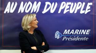 La présidente du Front national (FN) Marine Le Pen devant une affiche pour sa campagne électorale présidentielle de 2017, alors qu'elle inaugure son siège de campagne à Paris, en France, le 16 novembre 2016.