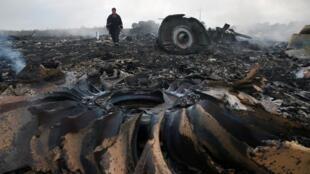 Un responsable des secours marche parmi les décombres du Boieng MH17, le 17 juillet 2014, près de Donetsk.