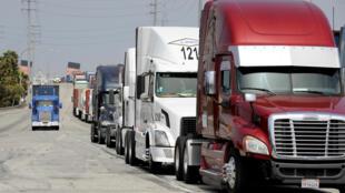 Xe chở containers đậu chờ containers từ Trung Quốc chuyển sang tại cảng Long Beach (California-Mỹ) ngày 04/04/2018.