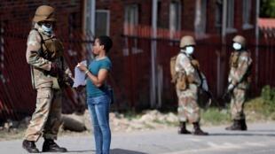 Une habitante du township d'Alexandra montre un justificatif à un élément des forces de défense nationale. Le 28 mars 2020.