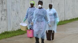 Des volontaires transportent des seaux de désinfectant jusqu'au nouveau centre de traitement Ebola, à Monrovia, le 25 septembre 2014.
