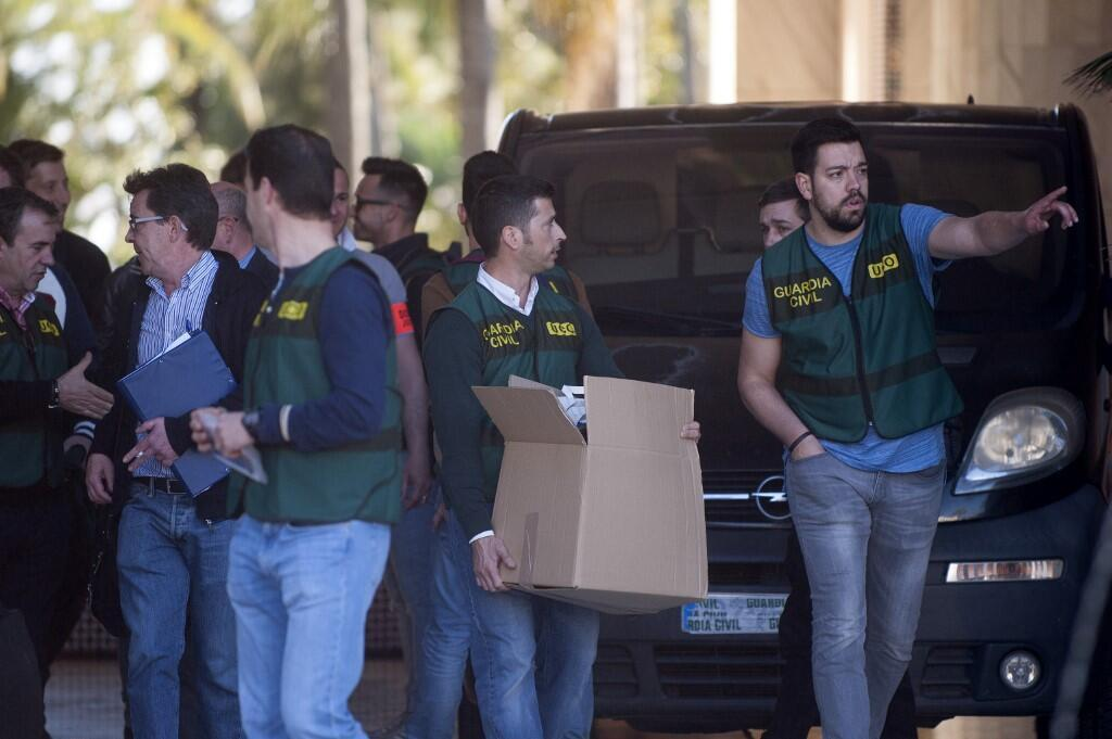A member of the Spanish Guardia civil carries a cardboard box during a raid targeting assets of Rifaat al-Assad and his family in Spain valued at 691 million euros.