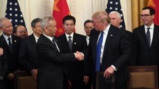 Naibu wa Waziri Mkuu wa China Liu He (kushoto) na Rais wa Marekani, Donald Trump (kulia) wakitia saini sehemu ya kwanza ya mkataba wa biashara kati ya Marekani na China.