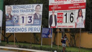 Un homme passe devant les affiches de la campagne politique alors que les Péruviens se rendent aux urnes dimanche pour choisir un nouveau Congrès, à Lima au Pérou, le 25 Janvier 2020.
