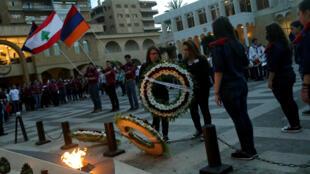 Des membres de la communauté arménienne au Liban déposent des couronnes de fleurs à l'entrée du mémorial aux martyrs de l'église Saint Stephano au nord de Beyrouth, pour rendre hommage à la veille du centenaire du génocide, le 23 avril 2015.