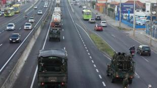 Des véhicules militaires accompagnent les camions de transport de produits pétroliers, le 28 mai 2018 sur l'autoroute de Porto Alegre.