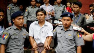Les deux journalistes birmans de Reuters Wa Lone et Kyaw Soe Oo escortés par la police après une comparution au tribunal de Rangoon, le 20 août 2018.