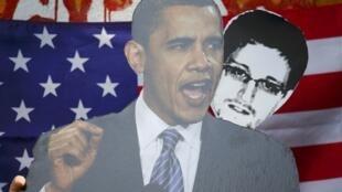 Ảnh Barack Obama (T) và Edward Snowden trên một biểu ngữ trong cuộc biểu tình phản đối ở Berlin, ngày 19/06/2013