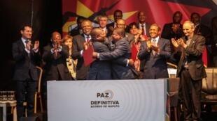 Le président mozambicain Filipe Nyusi et le chef de la Renamo Ossufo Momade s'étreignent après la signature d'un accord de paix dit définitif, le 6 août 2019 à Maputo.