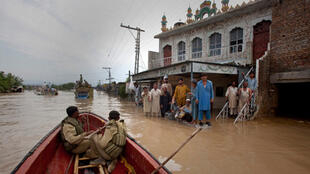 Residents of Nowshera who sheltered in a mosque wait to be evacuated by the army