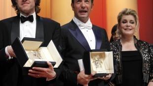 """Bill Pohlad, produtor de """"The Tree of Life"""", recebe a Palma de Ouro em nome de Terrence Malick. Ao lado, Jean Dujardin (melhor ator)  e Catherine Deneuve."""