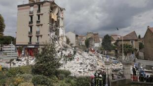 Bombeiros buscam um desaparecido em meio aos escombros do prédio que desabou na periferia de Paris.