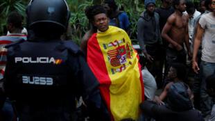 Migrante que cruzou cerca se enrola na bandeira espanhola