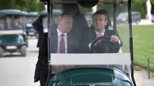 Tổng thống Pháp Emmanuel Macron (P) và tổng thống Nga Vladimir Putin trên đường thăm khu vườn lâu đài Versailles, ngày 29/05/2017.