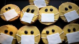 Unas galletas de caras con mascarillas, preparadas en la panadería Schuerener Backparadies de Dortmund, en el oeste de Alemania, el 26 de marzo de 2020 en plena pandemia del coronavirus COVID-19