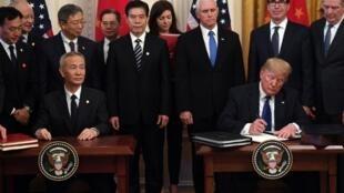 El viceprimer ministro chino Liu He y el presidente estadounidense Donald Trump firman la primera fase del acuerdo comercial entre ambos países.