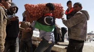 Anti-government demonstrators unload a shipment of humanitarian aid from Egypt at Tobruk, 14 March 2011