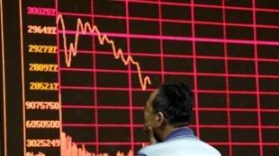 Un courtier regarde les actions chuter à la bourse de Shangaï, le 26 août 2015.