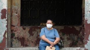 Une retraitée fait la queue pour pouvoir toucher sa pension mensuelle avant le début du couvre-feu, dans la ville équatorienne de Guayaquil, le 20 mars 2020