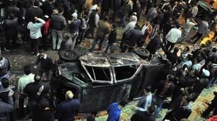 People gather around a damaged car outside Alexandria's Al-Qiddissin church, 1 January 2010