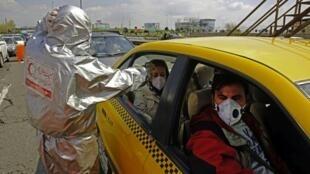 Afisa wa shirika la Msalaba Mwekundu kutoka Irani lakifanya vipimo kwa abiria wa teksi, Machi 26, 2020, karibu na Tehran.