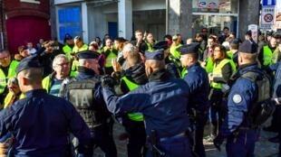 Des policiers anti-émeutes évacuent des manifestants portant des gilets jaunes, lors d'une manifestation contre la hausse des prix du carburant et de l'essence, le 9 novembre 2018.