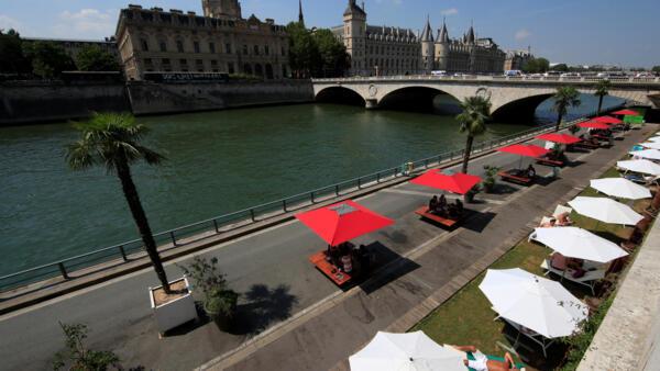 Espreguiçadeiras, guarda-sóis e palmeiras foram instalados às margens do rio Sena